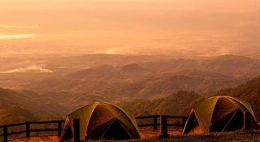 deux tentes se dressent sur fond de magnifique paysage de montagne avec la lumière chaude du coucher du soleil. photo