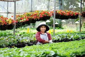 une agricultrice heureuse avec une tablette à la main se tient près d'une fleur dans la serre. technologie moderne pour les agriculteurs et la floriculture. photo