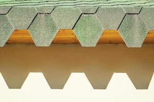 toit vert avec tuiles hexagonales. toit aux bords dentelés projetant des ombres dures sur le mur. photo