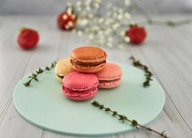 macarons colorés français. macarons pastel colorés sur fond clair avec des fraises fraîches. concept de flou artistique. photo