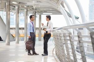 deux hommes d'affaires marchant et parlant dans la ville. photo