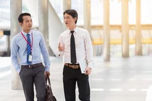 deux hommes d'affaires travaillent sur le trottoir avec un smartphone et un ordinateur portable pour le concept d'entreprise. photo