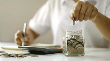 les gens d'affaires mettent des pièces de monnaie dans des bouteilles en verre, des idées de compte d'épargne et des économies d'argent. photo