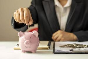 gros plan d'une femme d'affaires tenant une pièce de monnaie dans une tirelire, un concept d'économie d'argent pour la comptabilité financière. photo