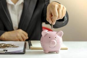 les femmes d'affaires qui détiennent étroitement des pièces dans une tirelire, notamment en appuyant sur une calculatrice pour des idées d'économie d'argent. photo