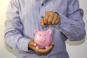 un homme d'affaires a mis une pièce de monnaie dans une tirelire rose et a économisé de l'argent pour planifier des idées pour de futurs fonds de retraite photo