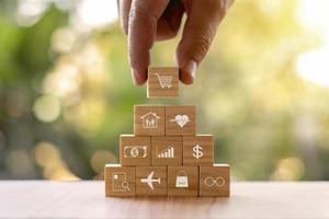blocs de bois triés à la main avec symboles de marchandises, idées de commerce en ligne. photo
