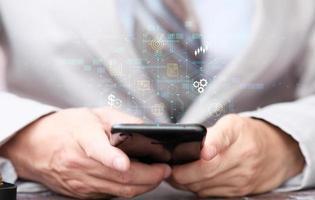 homme d'affaires utilisant un smartphone et une gestion des processus d'analyse des données de travail avec des tableaux et graphiques financiers et un tableau de bord marketing automatisé photo