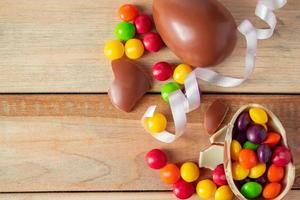 bonbons multicolores et œufs en chocolat de pâques sur un fond en bois clair. photo
