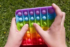 Jouet sensoriel anti-stress coloré push pop it dans les mains des enfants photo