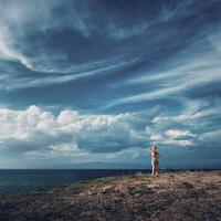 femme blonde debout au sommet de la colline et donnant sur la mer. beau ciel sur la mer égée, péninsule de kassandra, grèce. photo