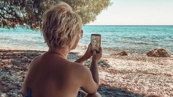 femme blonde faisant le selfie à la plage. femme faisant le selfie sur la plage sauvage à l'ombre d'un immense pin et regardant la mer Égée. photo