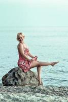 femme blonde heureuse dans une robe fleurie rougeâtre. femme assise et pose sur la grosse pierre au bord de la mer. photo
