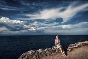 femme blonde au bord de la mer. jolie femme blonde assise sur le mur de pierre au bord de la mer. photo