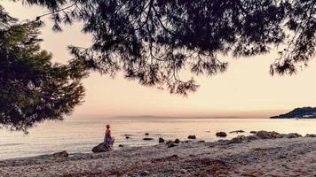 femme blonde en robe violette assise sur l'énorme rocher à côté de la mer, regardant le coucher de soleil et attendant quelque chose ou quelqu'un. photo