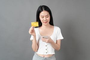 femme asiatique avec un visage heureux et présentant une carte de crédit en main montrant la confiance pour effectuer le paiement photo