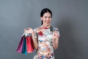 une femme asiatique porte une robe traditionnelle chinoise avec un sac à provisions et une carte de crédit photo