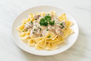 pâtes farfalle avec sauce crème blanche aux champignons - style cuisine italienne photo
