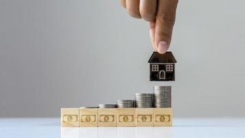 un tas de pièces sur un bloc de bois avec une icône d'argent et un concept de financement et d'investissement mobile de maison sur la société immobilière. photo