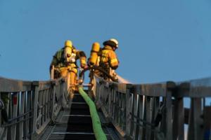 les pompiers grimpent à l'échelle contre la construction et éteignent un incendie photo