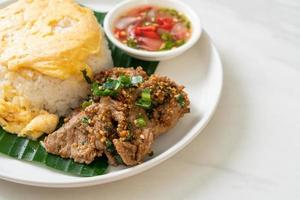 oeuf sur riz garni de porc grillé et sauce épicée - style cuisine asiatique photo