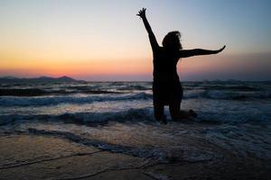 une fille sautant sur kos au coucher du soleil photo