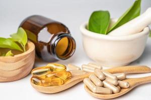 capsule biologique à base de plantes de médecine alternative avec vitamine e oméga 3 huile de poisson, minéral, médicament avec feuilles d'herbes suppléments naturels pour une bonne vie saine. photo