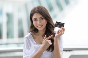 concept de vendredi noir, femme tenant une carte de crédit et souriant près du magasin photo