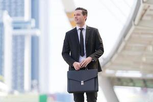 homme d'affaires prospère en réunion d'affaires tenant une mallette photo