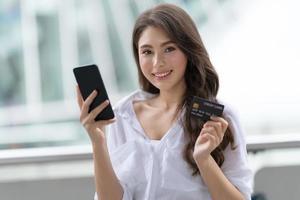 concept de vendredi noir, femme tenant un téléphone avec carte de crédit et souriant près du magasin photo