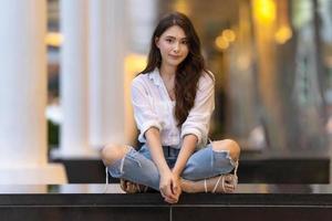 image d'une jeune femme heureuse assise sur le sol photo