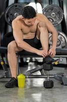 homme sportif s'entraînant avec des haltères dans une salle de sport, entraînement sportif de bodybuilder photo