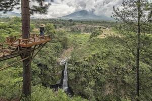 paysage indonésien en jave central. vue sur le volcan merapi et la cascade air terjun kedung kayang photo