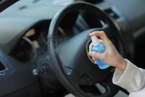 la main de la femme pulvérise de l'alcool, un spray désinfectant dans la voiture, la sécurité, prévient l'infection du virus covid 19, le coronavirus, la contamination des germes ou des bactéries. désinfectant à l'alcool, concept d'hygiène. photo