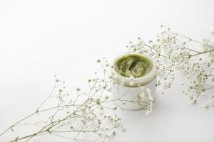 récipient en plastique ouvert avec de la crème et des fleurs sur fond blanc. crème pour le visage. crème aux herbes. produits cosmétiques. mise au point sélective. photo