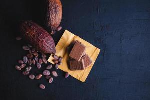 chocolat et fèves de cacao avec du cacao sur fond noir photo