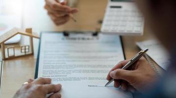 gros plan homme signant un contrat, un accord de travail, un client masculin signant des documents juridiques, prenant un prêt ou une hypothèque, achetant un bien immobilier, une assurance ou un investissement photo