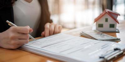 agent immobilier avec un modèle de maison mettant à la main un contrat de signature, ayez un contrat en place pour le protéger, signature d'accords modestes au bureau. concept immobilier, déménagement ou location de propriété photo