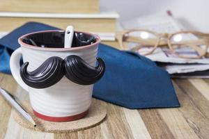 tasse avec moustache sur table en bois pour le concept de la fête des pères photo