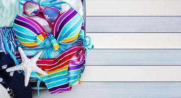bikini coloré et vêtements dans les bagages sur le fond en bois photo