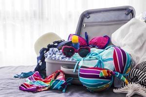 bikini coloré et vêtements dans les bagages sur le lit photo