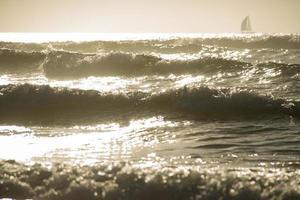 vagues de l'océan sous le coucher du soleil avec forme de voilier sur l'horison photo