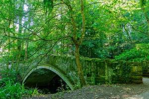 Vieux pont de pierre sur ruisseau dans le parc desmond dene, Newcastle, Royaume-Uni photo