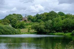 Étang et maison traditionnelle près de la cabane des admissions dans le parc de Lyme, Disley à Cheshire, Royaume-Uni photo