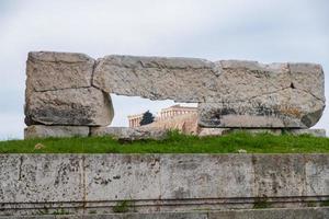 ruines de l'ancien temple de zeus olympien à athènes avec la colline de l'acropole en arrière-plan photo