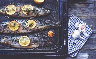 poisson maquereau frais cuit au four, avec citron et assaisonnement, sur une plaque à pâtisserie photo