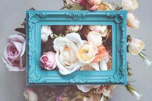 composition faite de cadre photo et de fleurs artificielles aux couleurs pastel