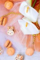 macarons orange fourrés au chocolat et macarons lapin de pâques, sur fond de tulle orange photo