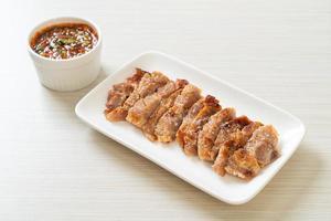 cou de porc grillé ou cou de porc bouilli au charbon de bois avec trempette thaï épicée photo