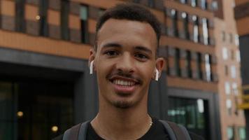 Portrait de jeune homme portant des écouteurs sans fil en riant photo